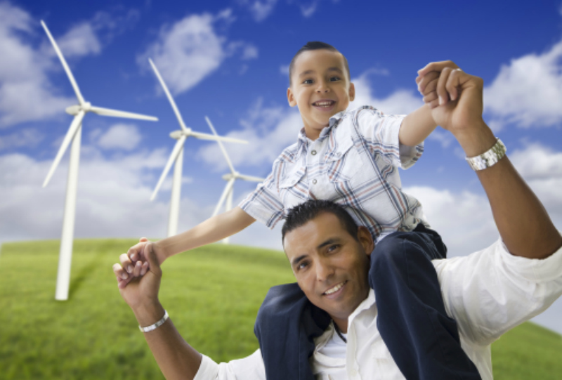 Son on dad's shoulders in front of wind turbines