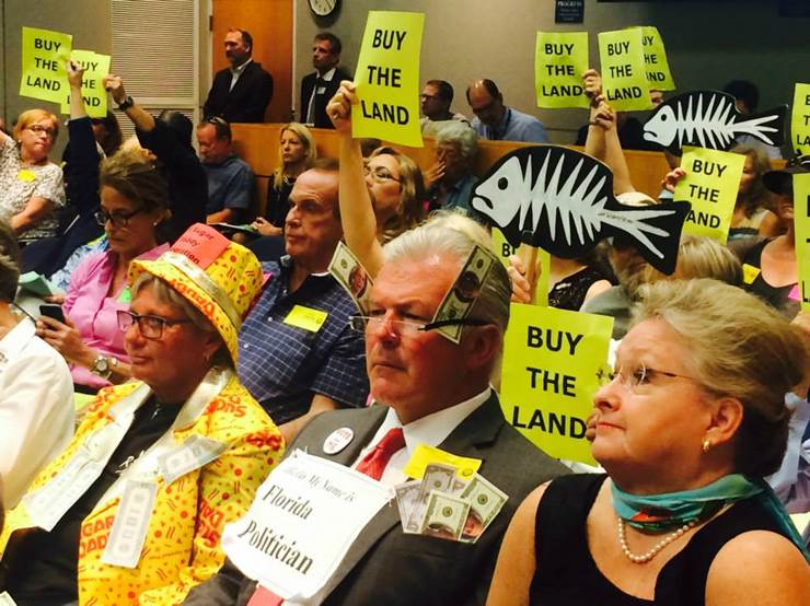 "Crowd at public hearing with ""Buy the Land"" signs"
